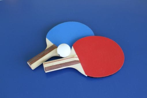 Two table tennis paddles with ball