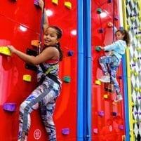 Girls Climbing Up Rock Wall