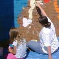 Teacher and pupil completing mural