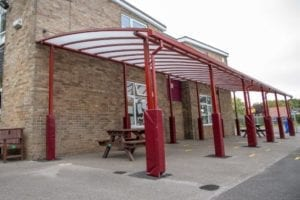 Red curved roof shelter we installed at Covingham Park Primary School