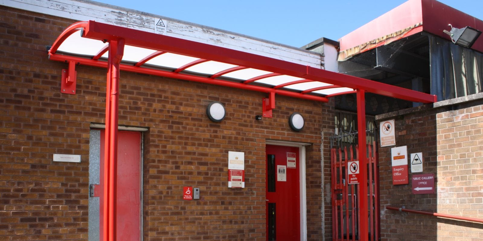 Red curved roof canopy we designed for Royal Mail Middleton